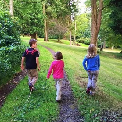three children walking together on a dirt road in nature
