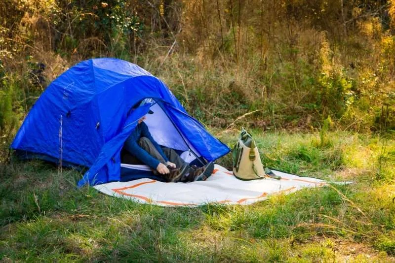 man in blue tent with camping mat