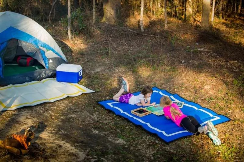 2 girls lying on camping mat at campsite
