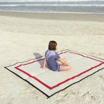 child sitting on Mountain Mat at the beach on sand