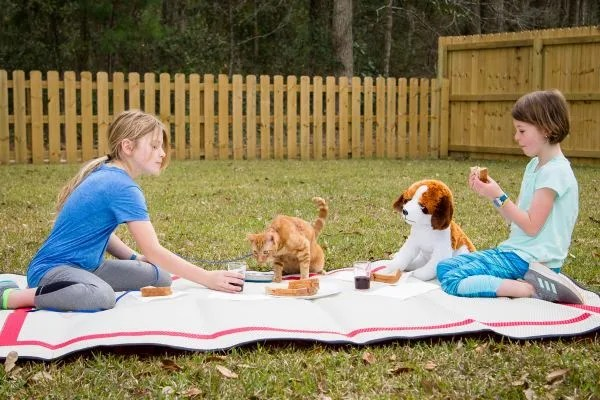 two girls having a picnic on an outdoor picnic mat