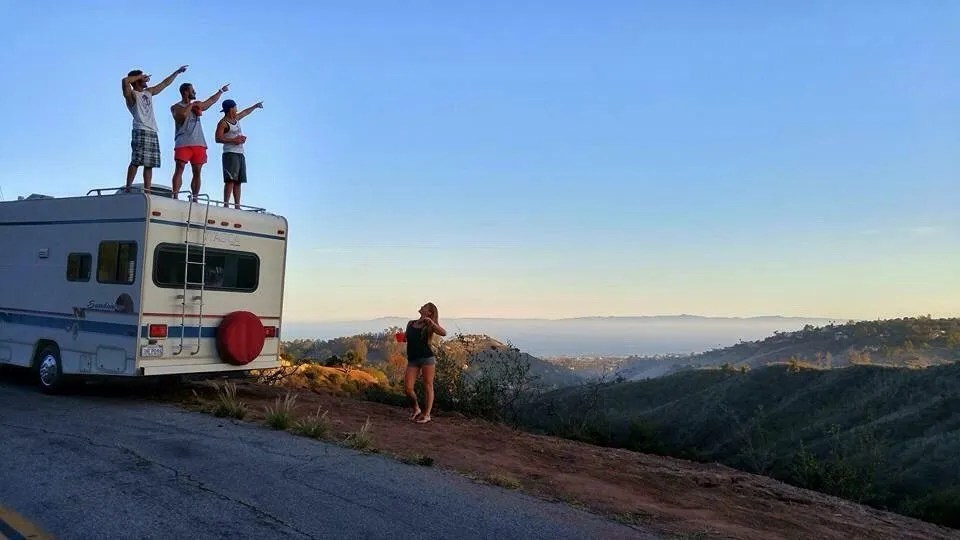 people standing on top of a RV