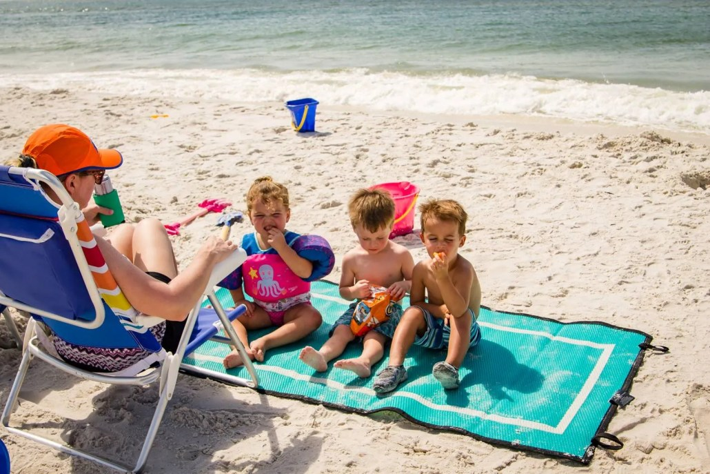 3 children eating snacks at beach on a teal sand-proof beach blanket