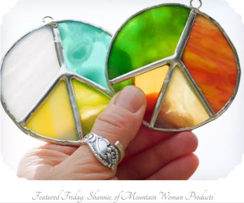 hand holding stained glass peace sign suncatchers