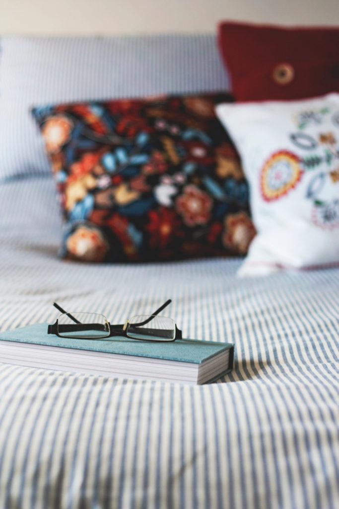 pillows a book and glasses on a bed