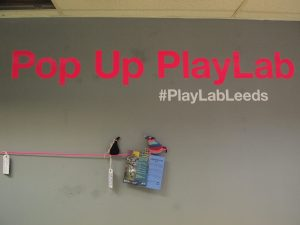 Fury and Ratvaark balance on a string under the sign for the Pop Up Playlab.