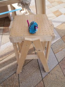 Ofelia sits on a simply constructed wooden stool