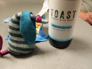 Ofelia looks at a bottle of Toast beer, made from waste bread