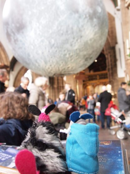 Dim and Matilda look at a huge model of the moon in the cathedral