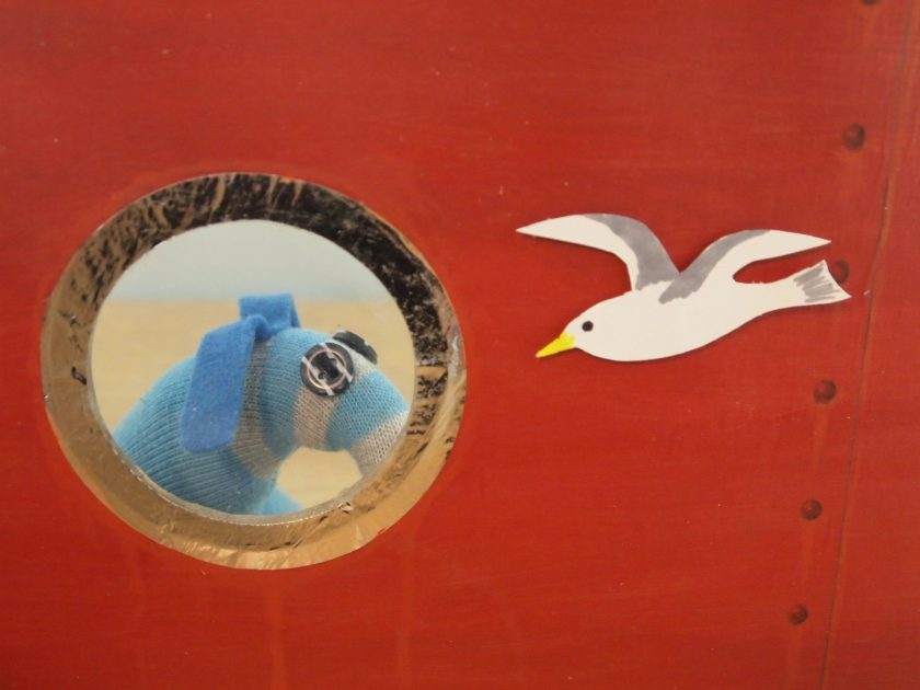 From outside the ship, we can see Arnold looking through the porthole as a gull flies alongside.