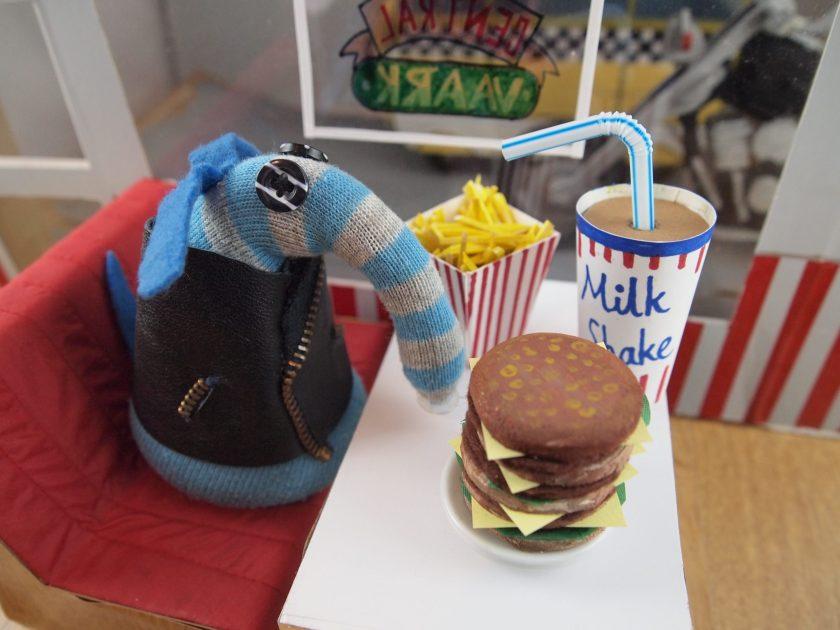 Arnold tucks into a huge burger, a big box of fries and a large milkshake.