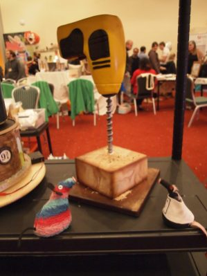 Ratvaark and Fury look at a cake made to look like a drill drilling into wood