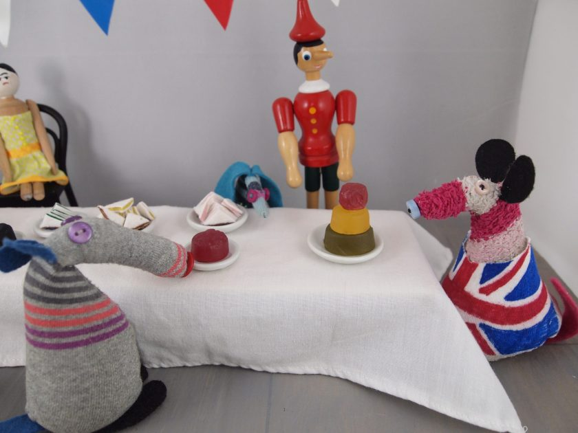 Dim and Matilda, in a Union Jack dress, put out plates of wine gums for jellies