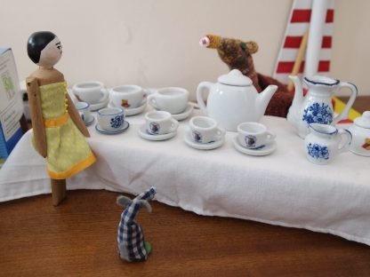 Esther is serving tea in cups and saucers from a long white table