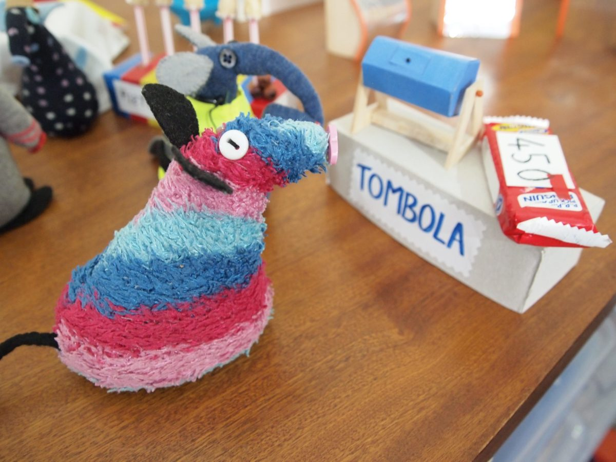 Ratvaark looks at the tombola stall with a tumbler and a penguin biscuit with a numbered ticket on it.