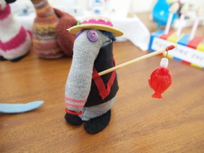 Dim is dressed in a black smock with a sash, and a red fish balloon on a stick