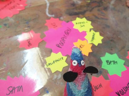 Ratvaark looks at a table with bright paper stars with names on them