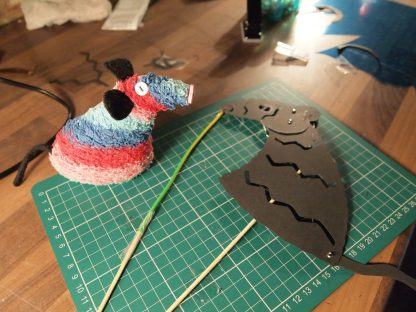 Ratvaark looks at a paper cut out shape,