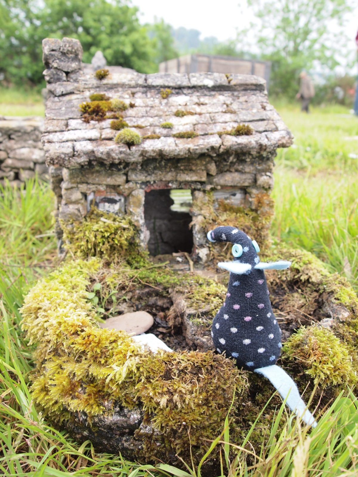 Winston looks at a little concrete garden ornament in the shape of a tumbledown cottage