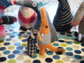 Microvaark greets Smigling a little felted creature with a long nose and wide open arms