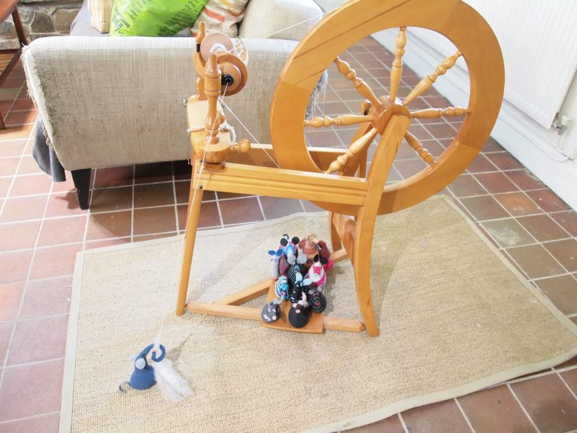 There is a spinning wheel, with all the vaarks sitting on the treadle and Ernest spinning a thread