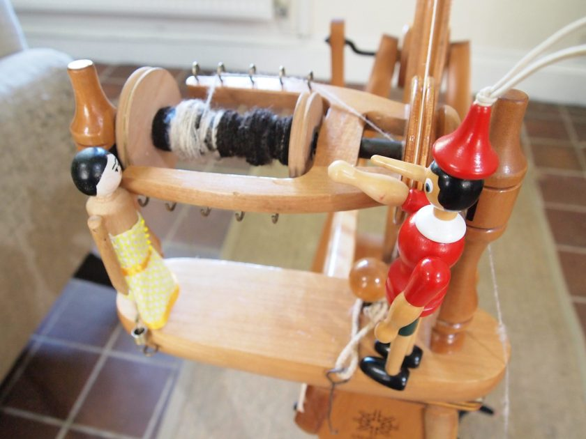 Peggy and Gino look at the bobbin with thread on it.
