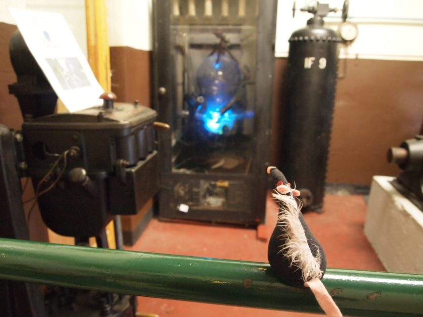 Fury looks at a bright blue light arcing through a glass tube