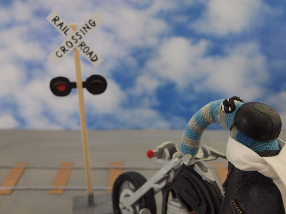 Arnold pulls up on his bike at a railroad crossing sign