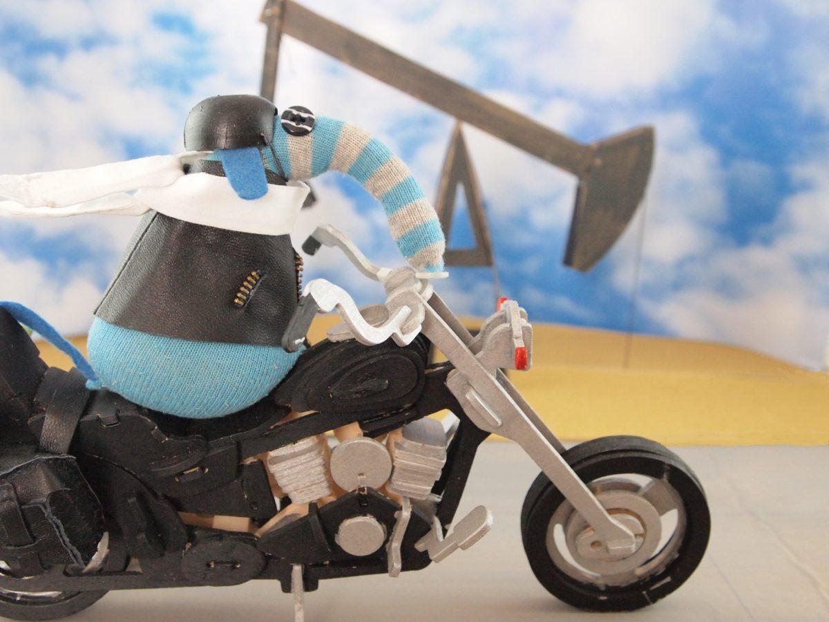 Arnold rides his motorbike beside a nodding donkey oil pump