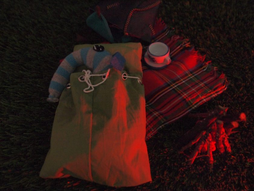 Arnold sleeps in his bivvy bag in the fire glow