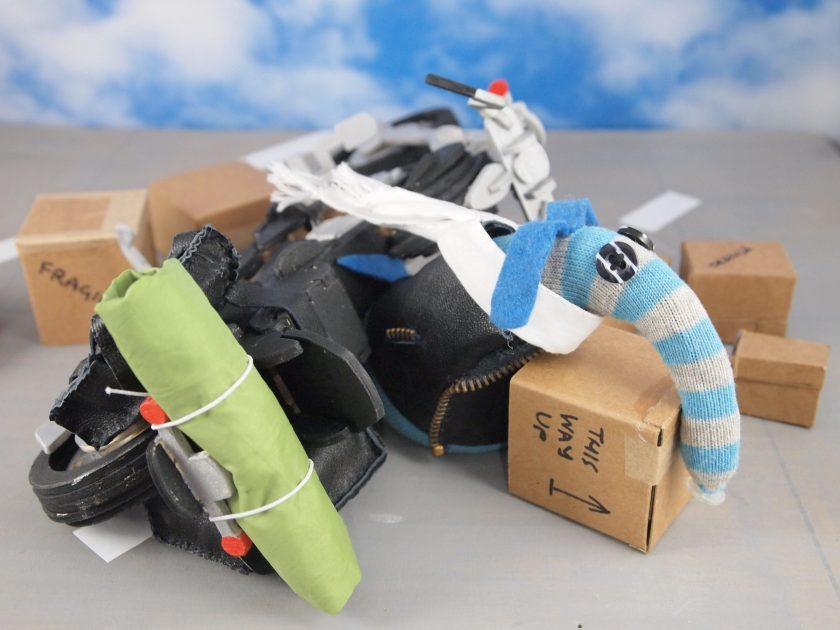 The bike is tipped over, and Arnold lies across a box