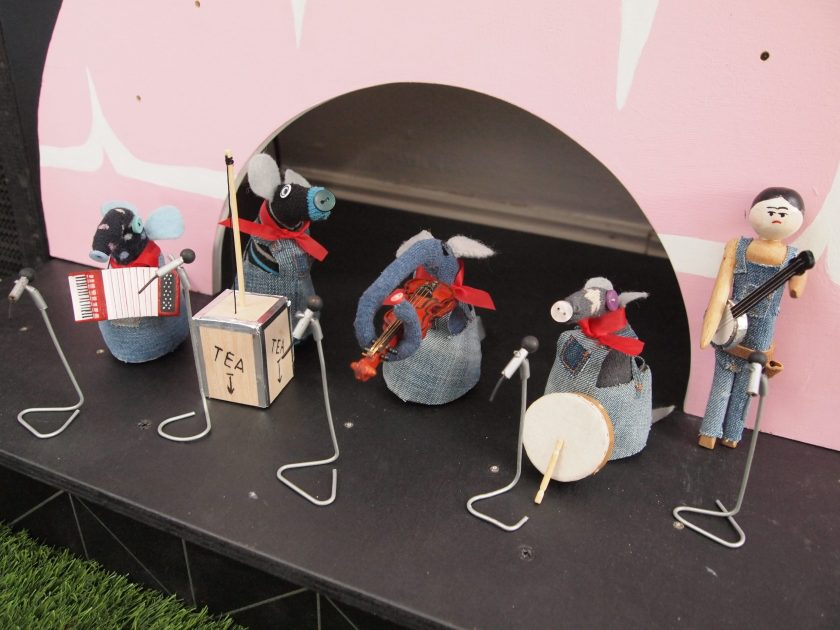 Vaarks and Peggy are dressed in dungarees, playing the accordian, tea chest bass, violin, drum and banjo