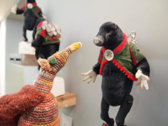 Esther looks at a textile sculpture of a mole in a velvet jacket