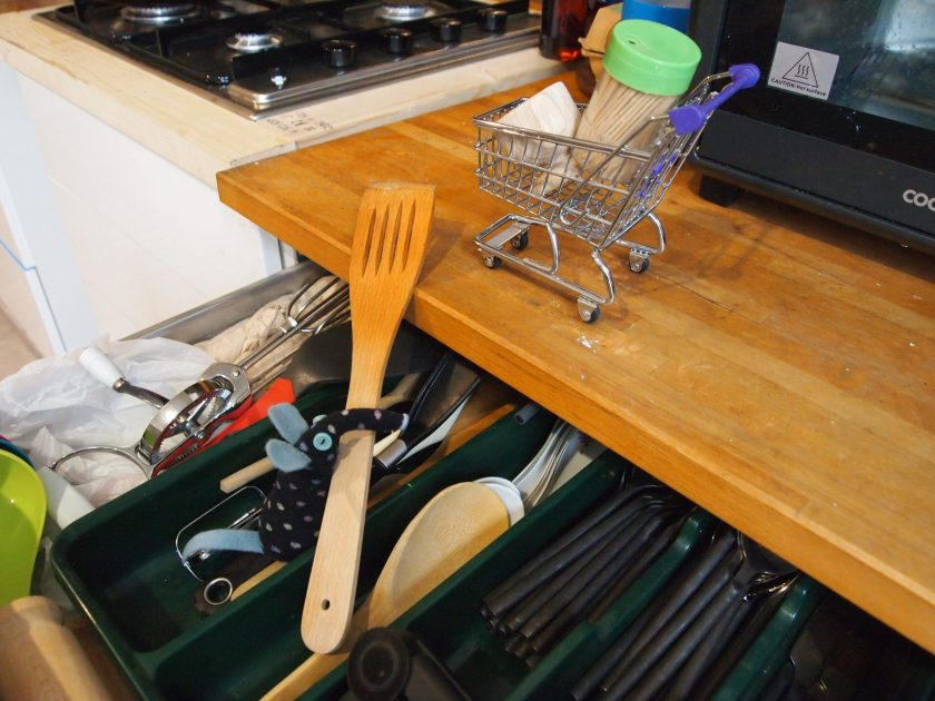 Winston gets a wooden spatula out of the cutlery drawer to add to an egg cup and a pack of toothpicks in his trolley