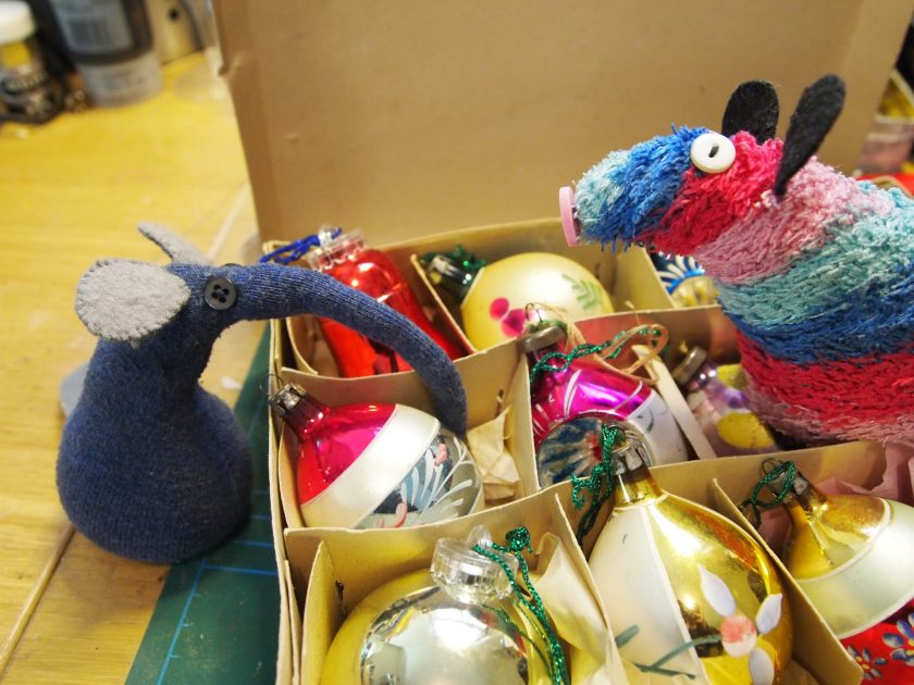 Ernest and Ratvaark choose an antique glass bauble from a box.