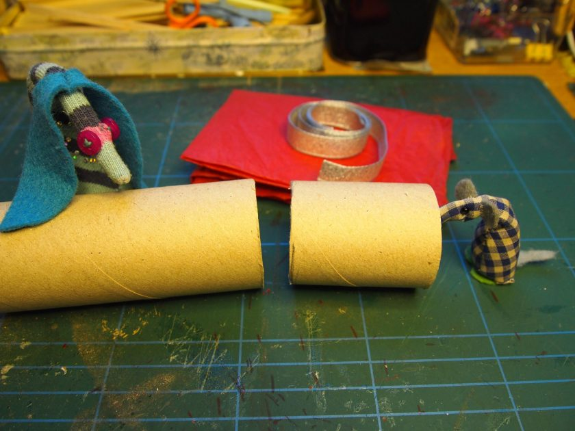 Ofelia and Microvaark look at some pieces of toilet roll tube, tissue paper and ribbon.