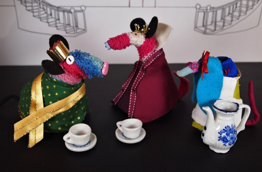 Ratvaark is dressed as a prince talking to the queen, as Snow White serves tea