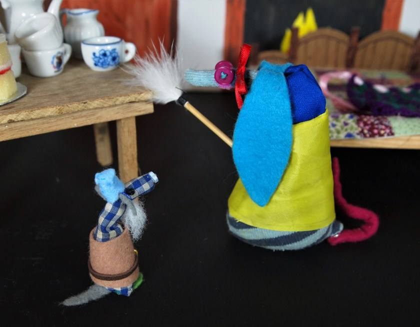 Snow White dusts the house with a feather duster