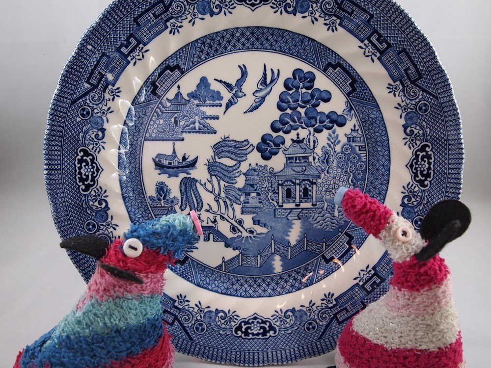 Ratvaark and Matilda hold up a Willow Pattern plate.