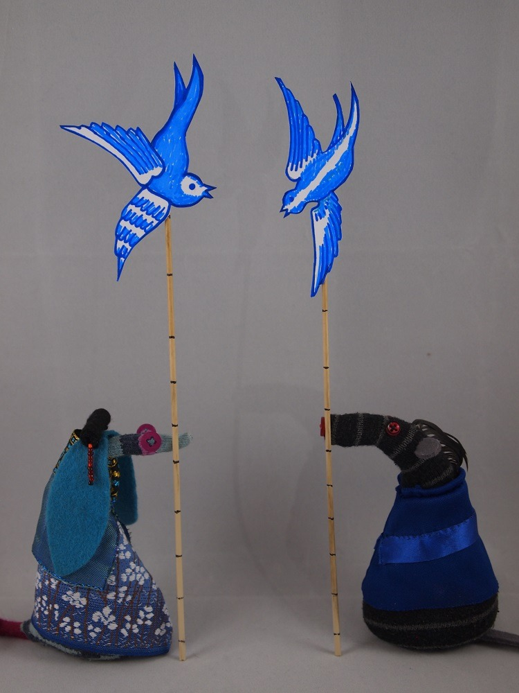 Bernard and Ofelia hold long bamboo sticks, with painted blue birds stuck to the top.