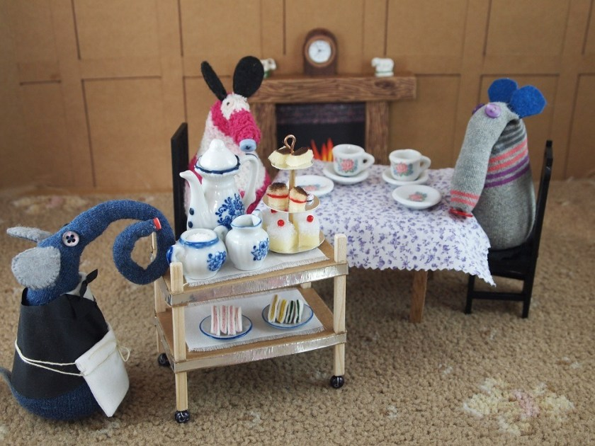 The waiter pushes a trolley to the table with tea, plates of sandwiches and a three tiered stand of cakes