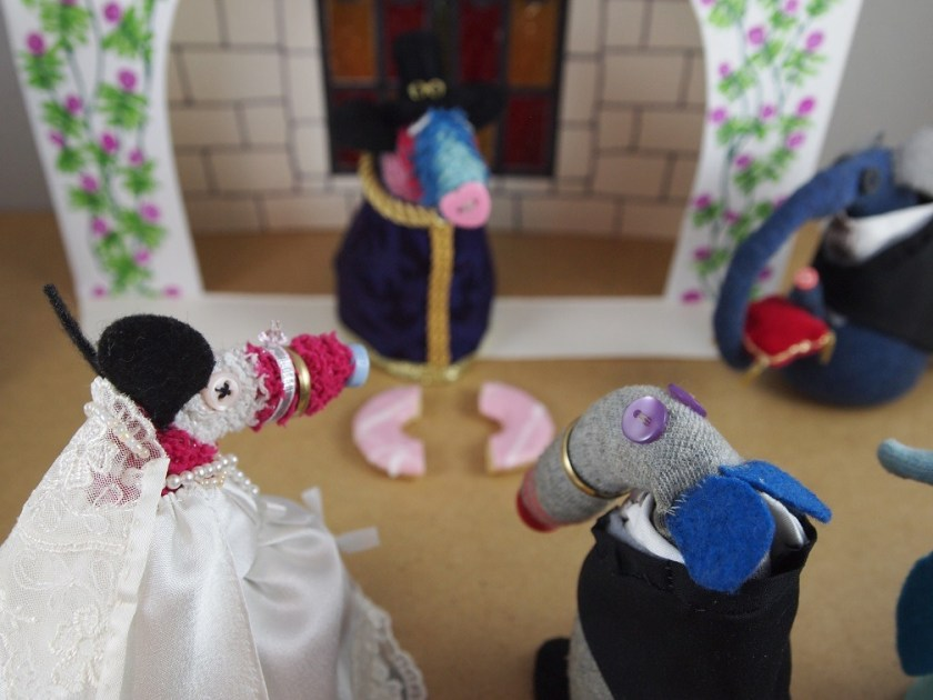 The couple look at Ratvaark as he produces a Party Ring biscuit broken in two
