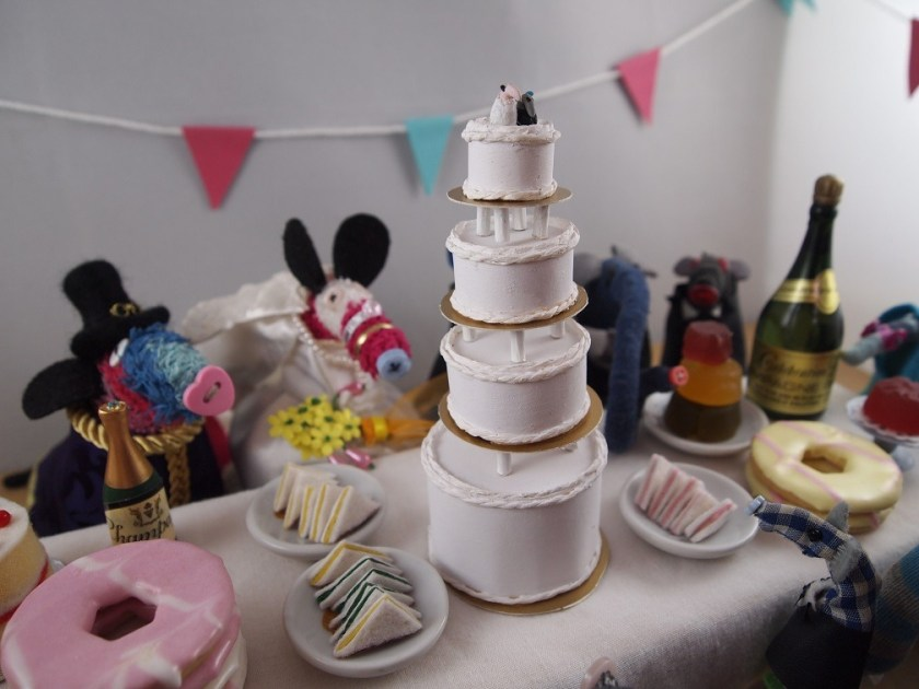 Everyone is at a reception with a table laden with food, and a four tiered wedding cake