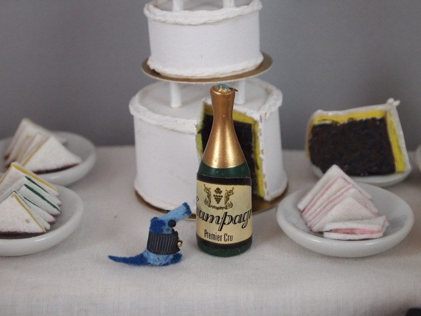 Nano is on the table looking at a bottle of champagne