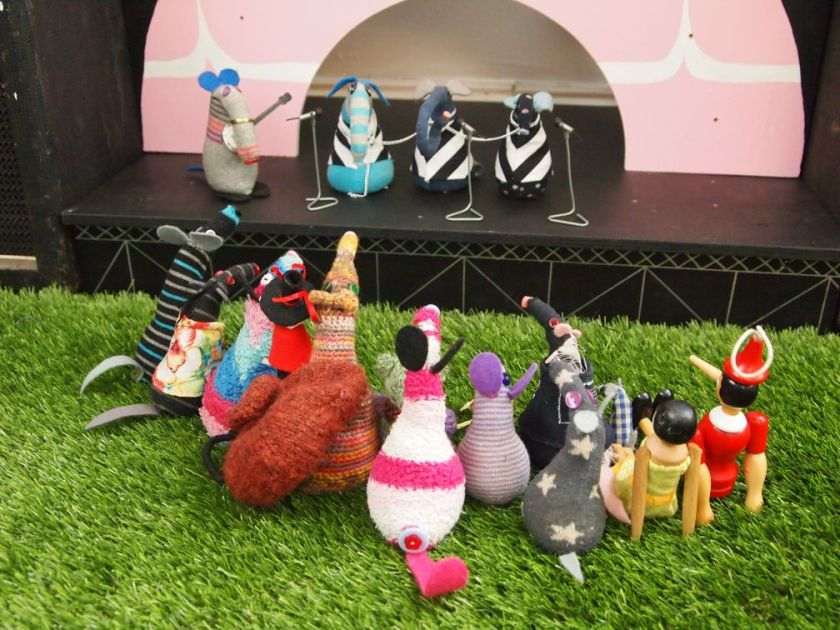 the vaarks look at the stage as dim plays banjo for three vaarks in black and white striped costumes
