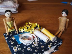Peggy sits with another wooden doll, and a pile of fabric and sewing things