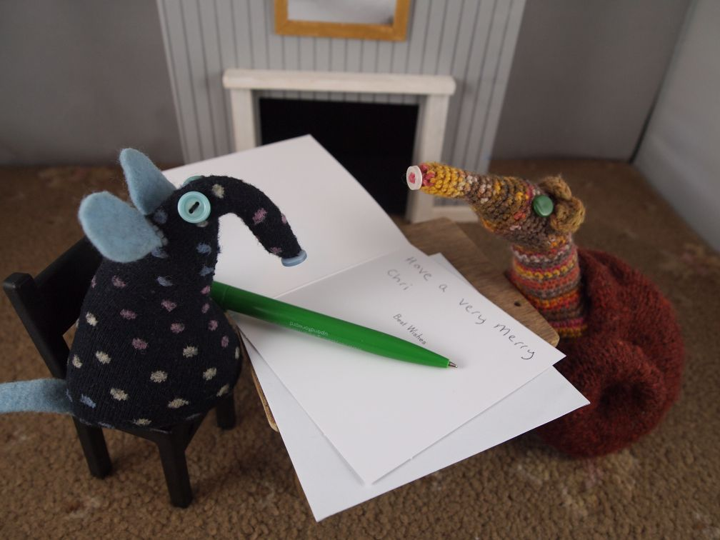 """Winston sits at a table with a card and pen, talking to Esther, He's written """"Have a very merry Chri"""" so far."""