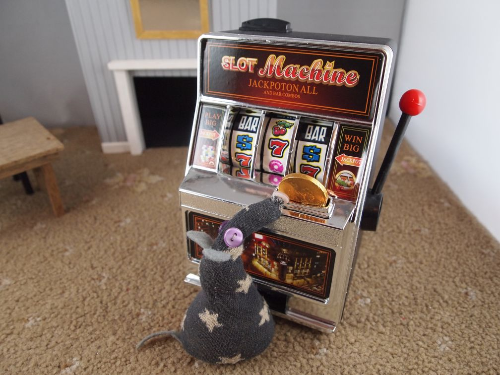 Vincent takes his coin to a mini fruit machine, and slots the coin in