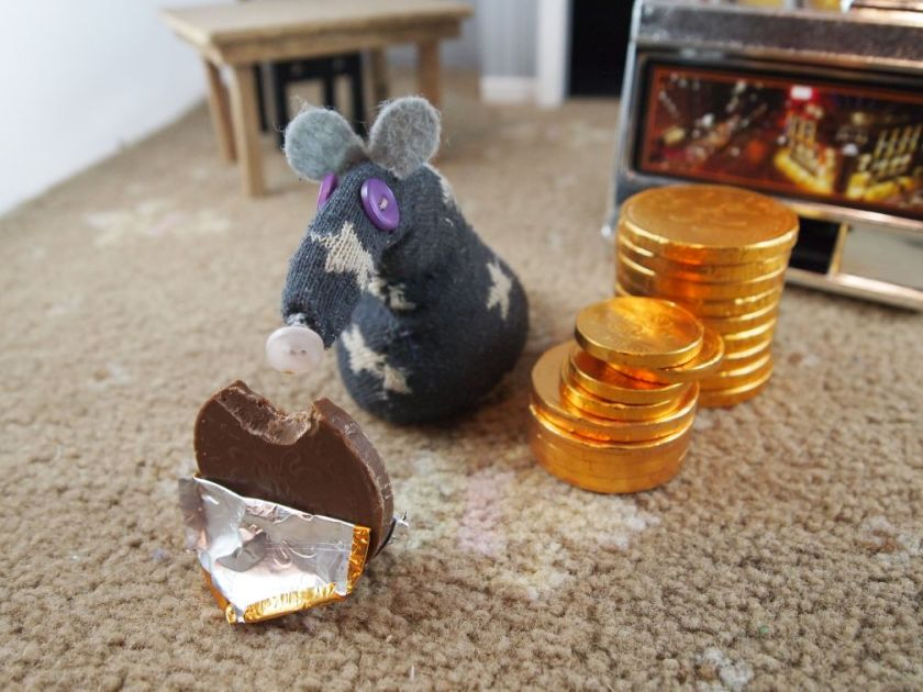 Vincent stacks up all the coins, and peels the foil off one to nibble it.