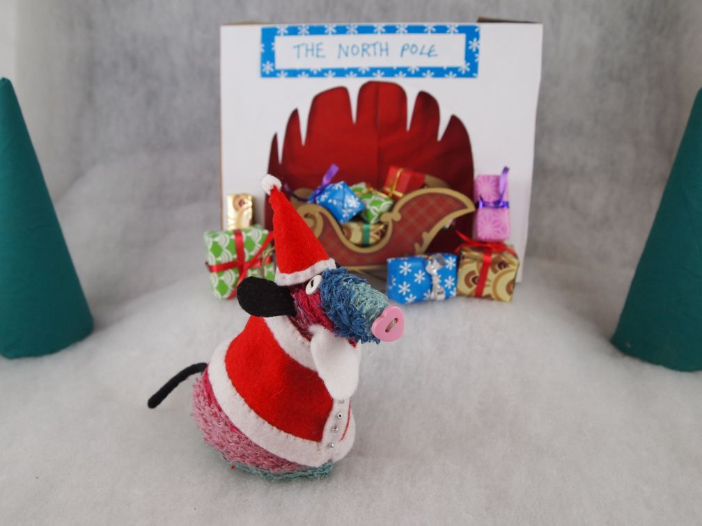 Ratvaark is dressed as Santa in a snowy scene in front of a sleigh of parcels and a grotto marked The North Pole